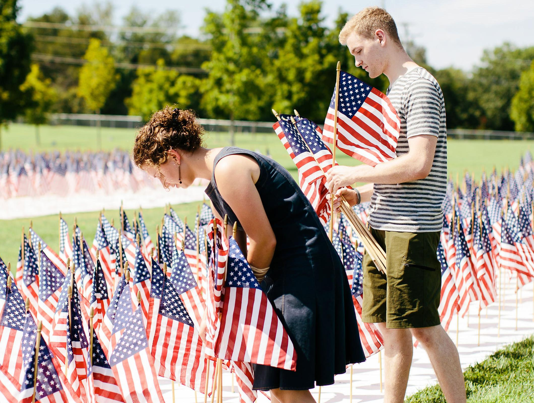 Students placing American flags at 9/11 Memorial Service at the Lest We Forget 9/11 Memorial