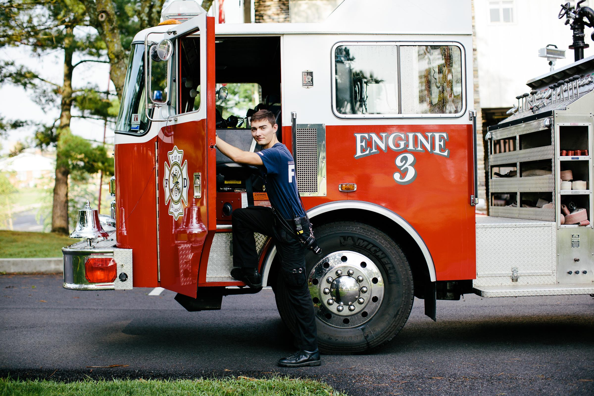 Fire Department student worker standing by a fire engine