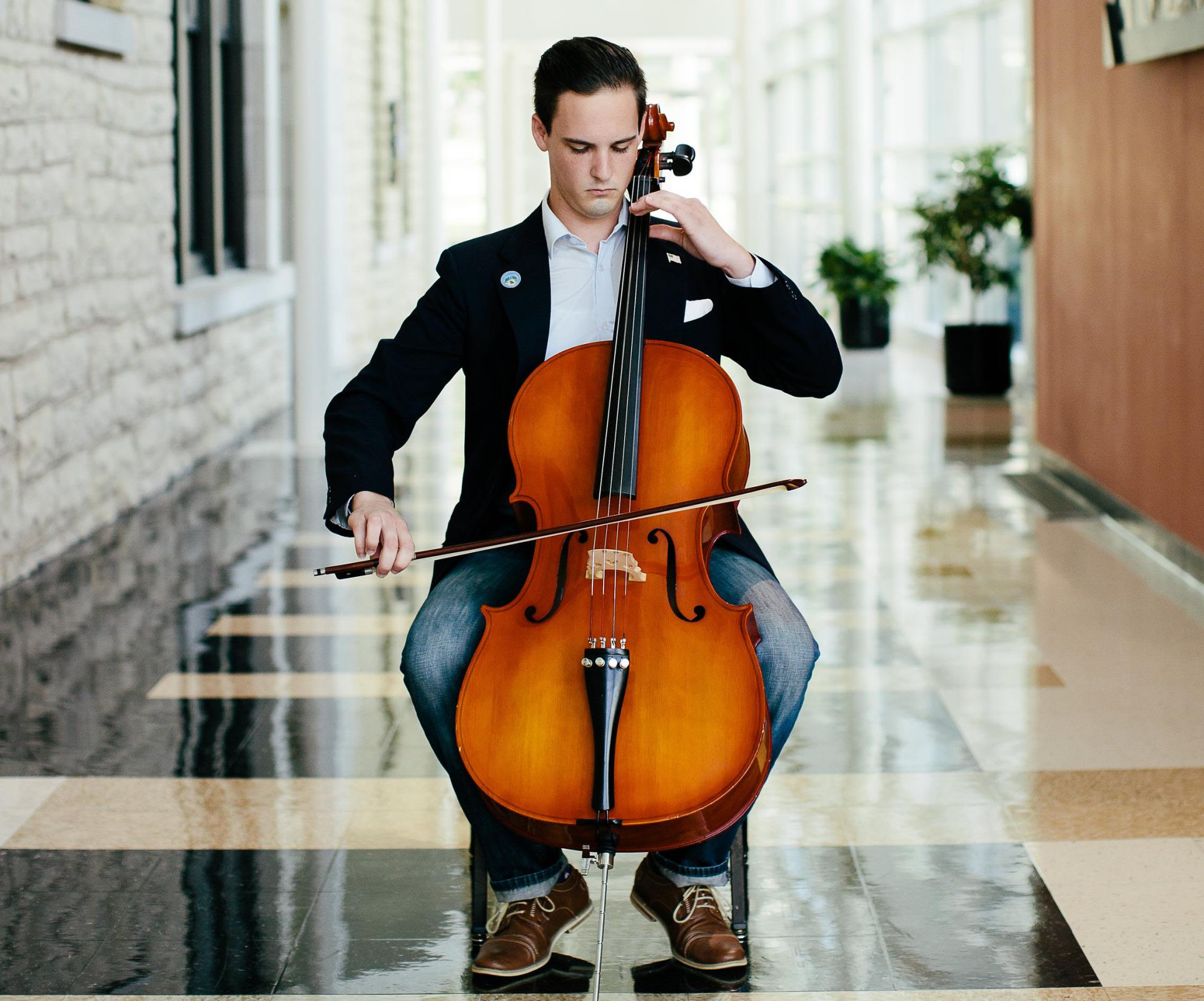 Student playing a cello in the Music Building