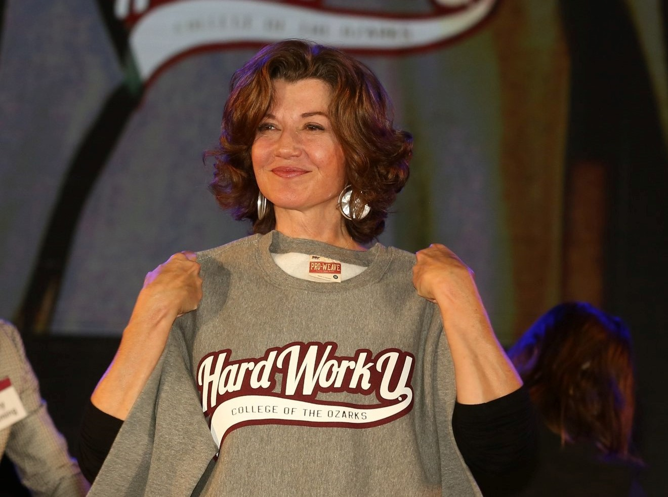Amy Grant holding up Hard Work U sweatshirt during a visit to College of the Ozarks
