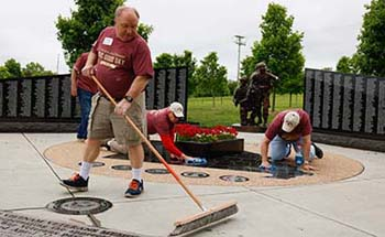 Alumni and veterans cleaning and polishing memorials at Patriots Park