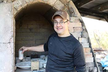 College of the Ozarks assistant professor of art places pottery inside the kiln