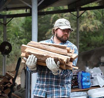 C of O alumnus carries wood to fire up the kilns